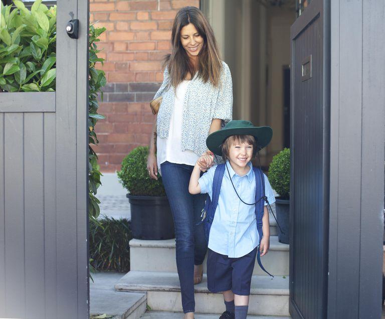 Australian mother walking school boy in uniform