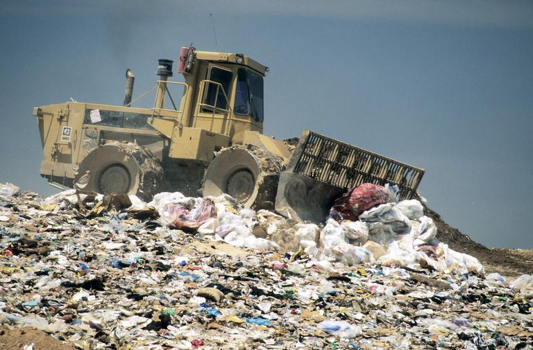 Compactor pushing trash at landfill
