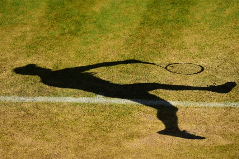 Player's shadow on a worn grass tennis court