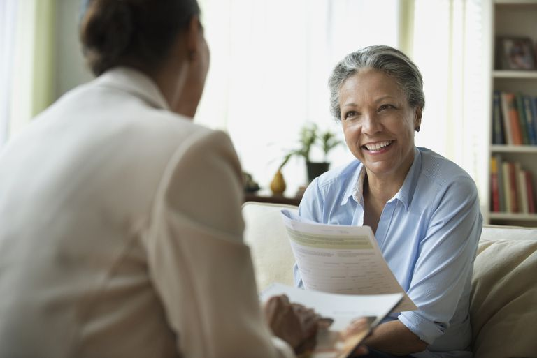 Hispanic saleswoman talking to client in living room