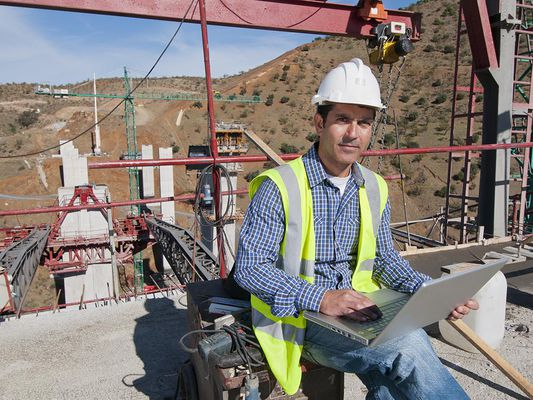 Construction worker using laptop at construction site