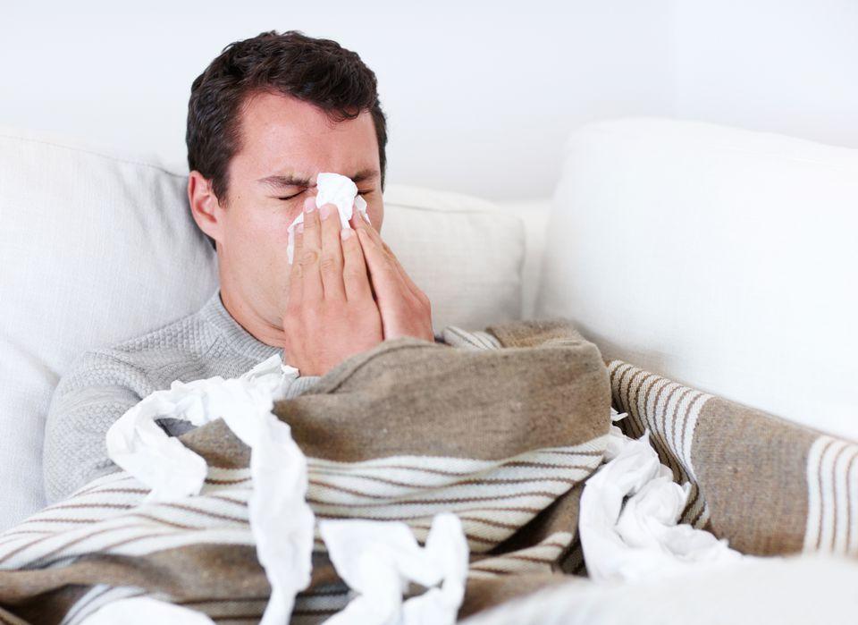 Sick bedridden man blowing his nose