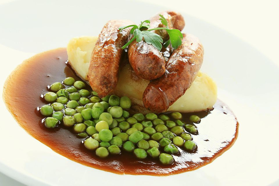 Sausage mash peas and gravy on white plate