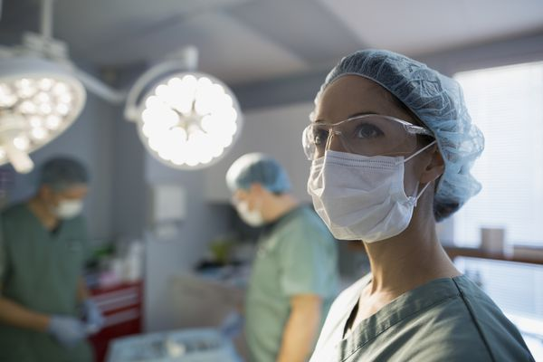 Pensive surgeon looking away in operating room