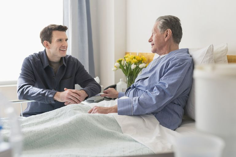 Caucasian son visiting father in hospital