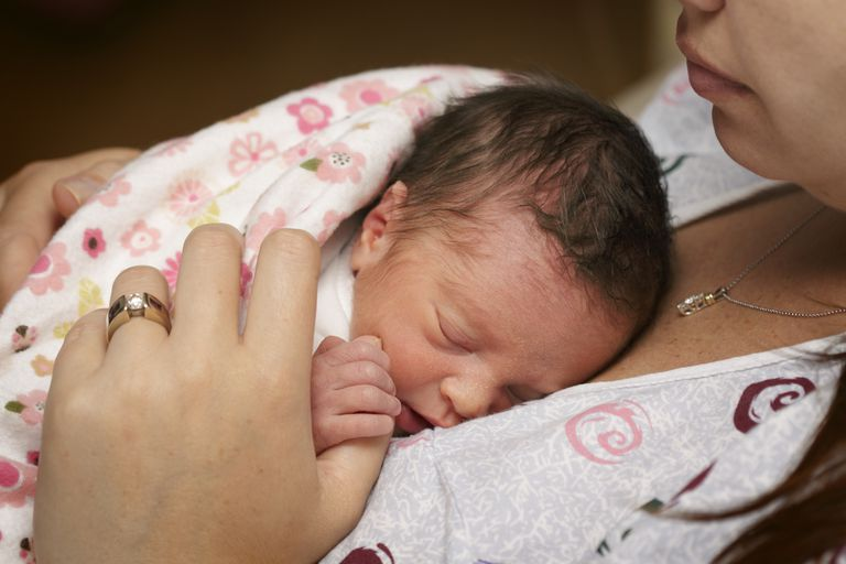 Mother holding premature baby.