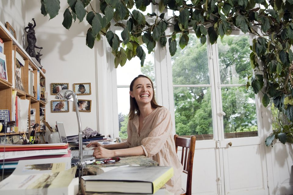 woman laughs at desk, surrounded by plants