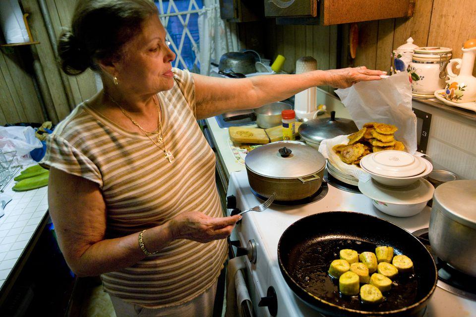 Puerto Rican Woman Fries Tostones (Plaintains)