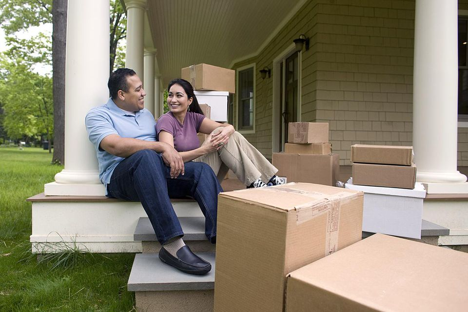 Happy couple with boxes, talking on porch
