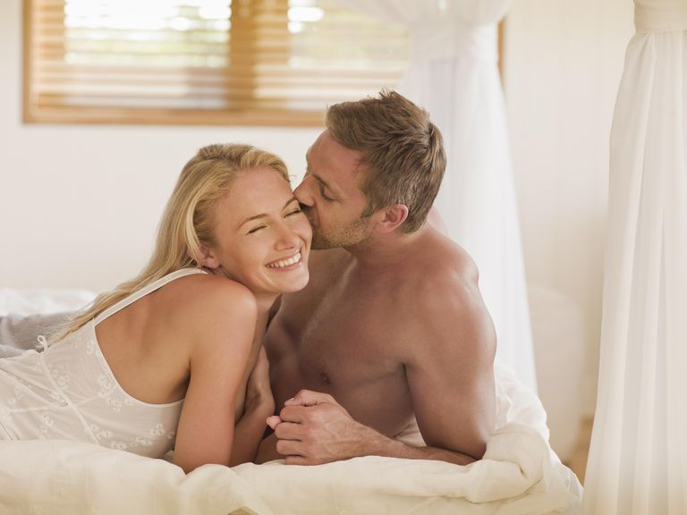 Man kissing woman lying on bed