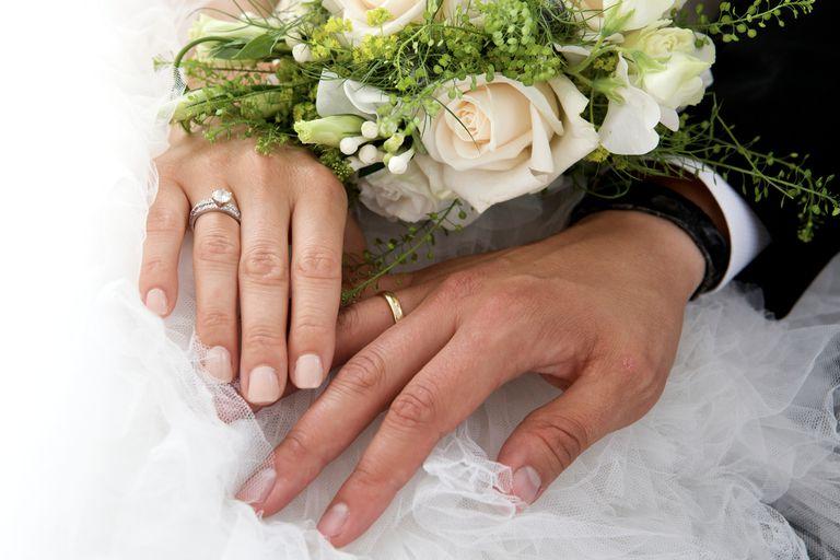Manos de recién casados con anillos de matrimonio