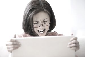 A woman clutching a laptop monitor and looking irritated.