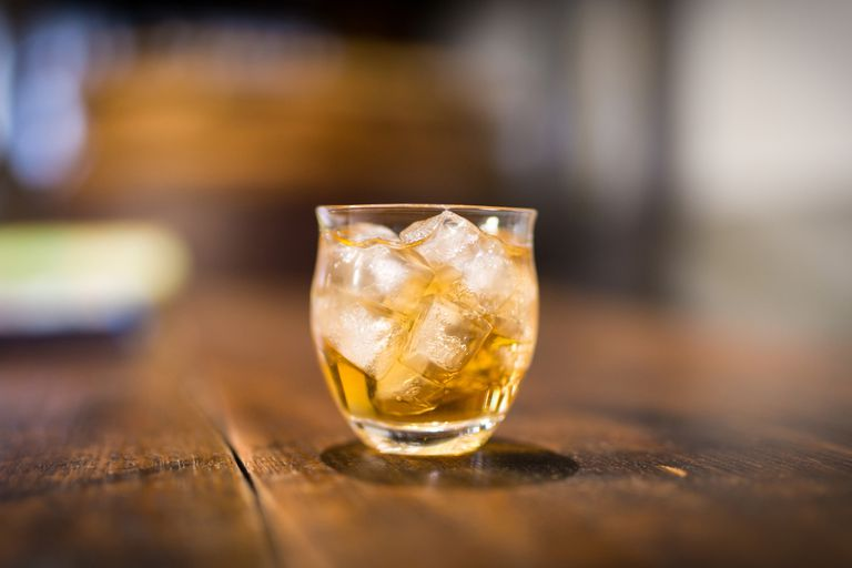 Glass of alcohol on wooden table