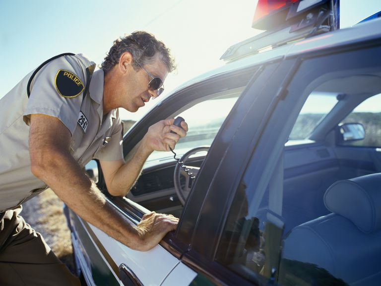 Close-up of a policeman standing near a car and looking through window