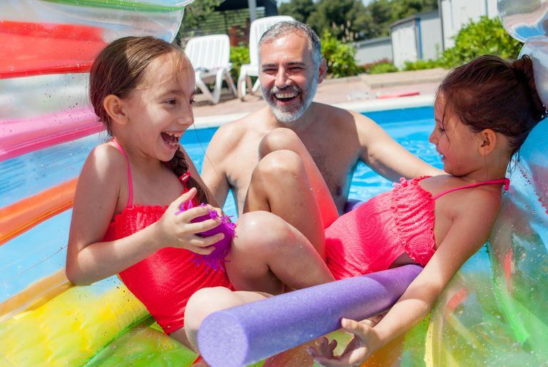 Father With Two Daughter And The Water Wheel In The Swimming Pool