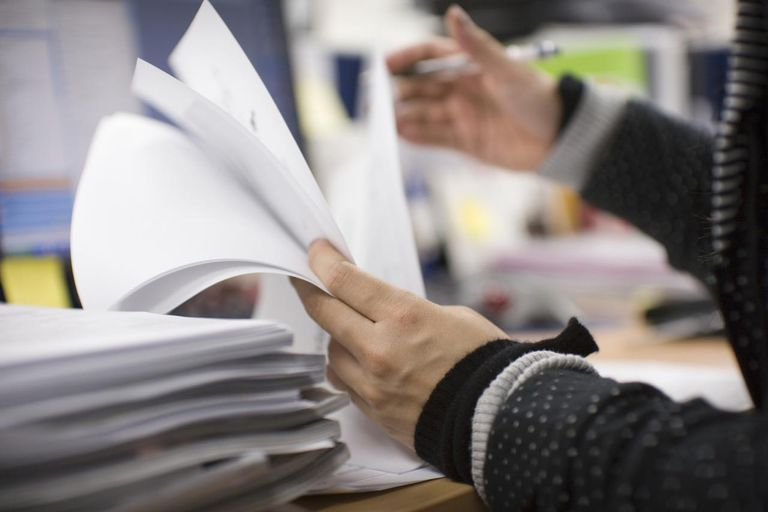 Office worker checking documents on desk, mid section, side view
