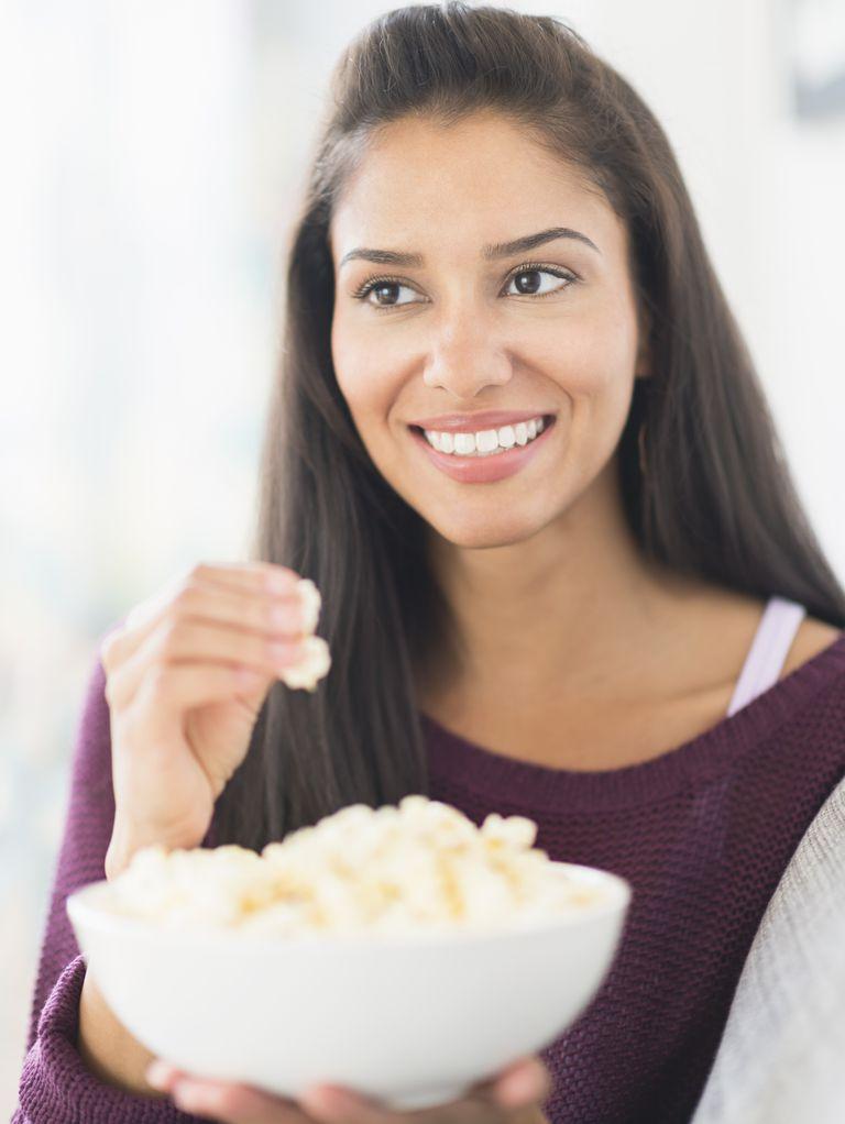 Hispanic woman eating popcorn