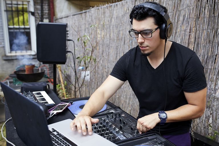 Hispanic dj playing music in backyard