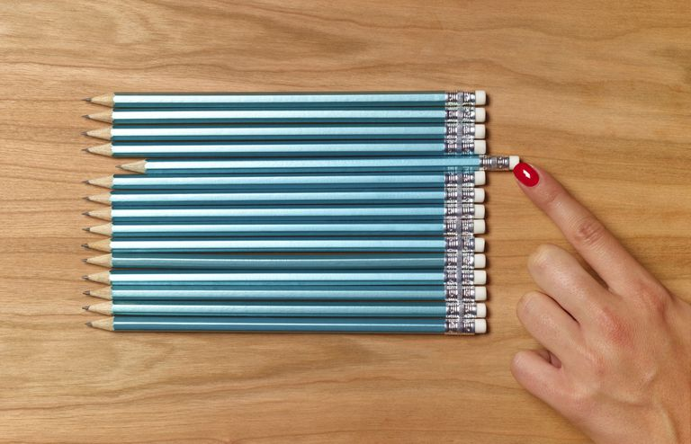 Pencils being precisely lined up on a desk.
