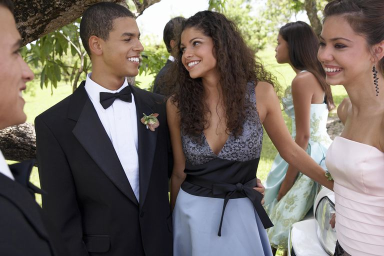 Teenage couple (15-17) in evening dress with friends, smiling