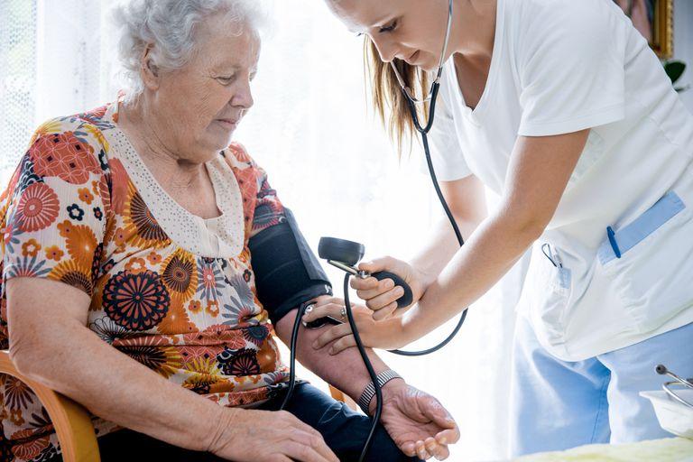 Nurse checking senior woman's blood pressure