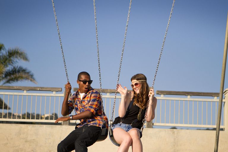Two Friends On Swings At Beach
