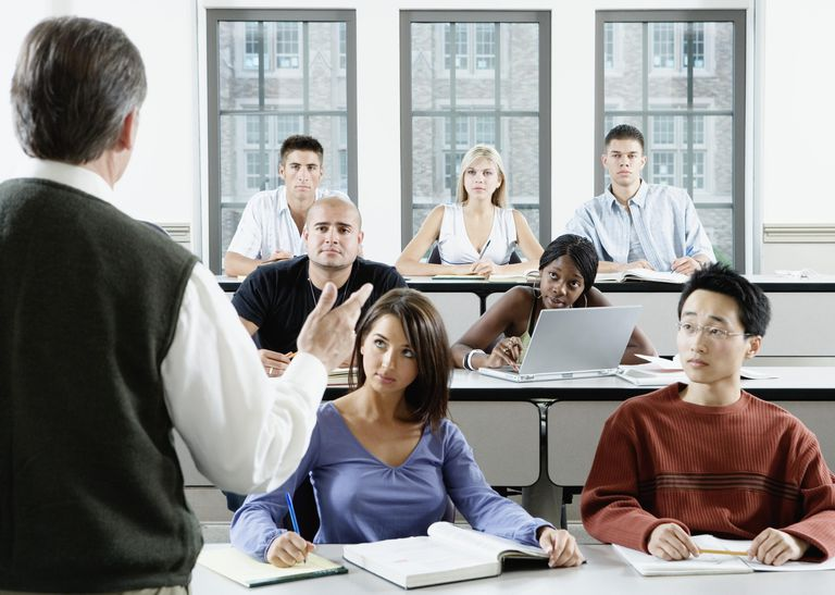 Male professor addressing group of college students in classroom