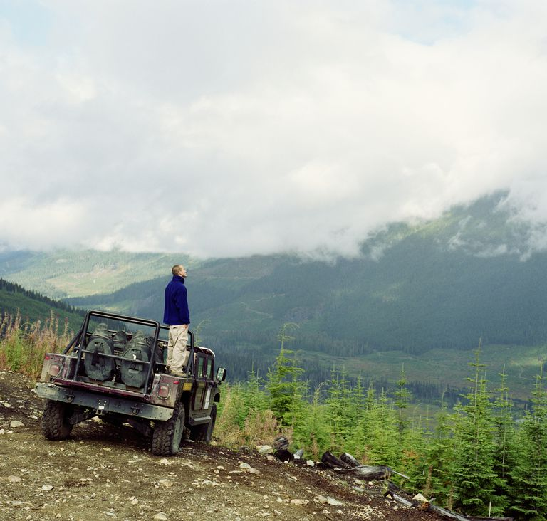 Man standing in back of off road vehicle, looking at mountain view