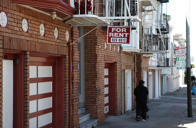 A sign advertising an apartment for rent hangs from a fire escape in front of an apartment building
