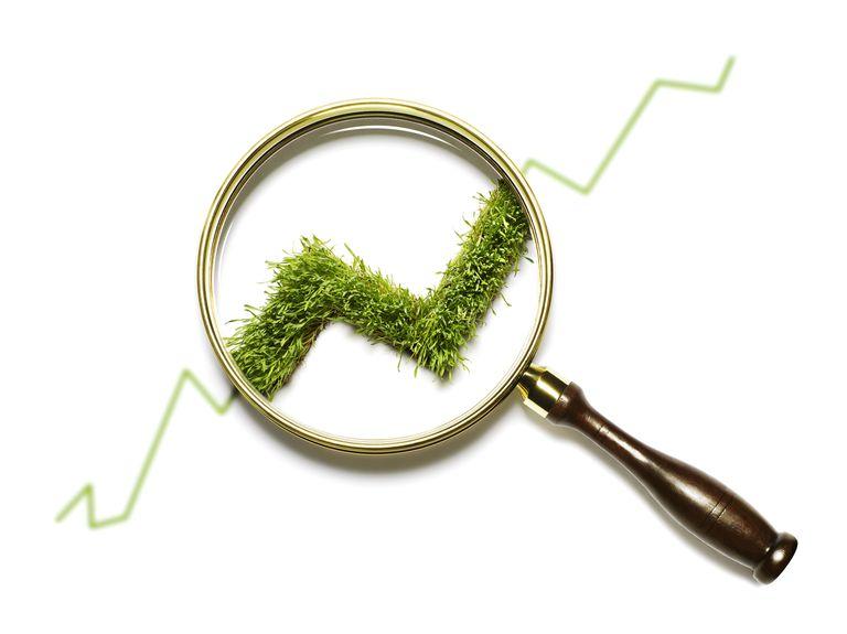magnifying glass on rising stock symbol