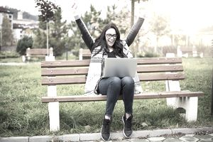 Happy woman with laptop on park bench
