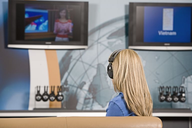 A woman watching TV while wearing wireless headphones