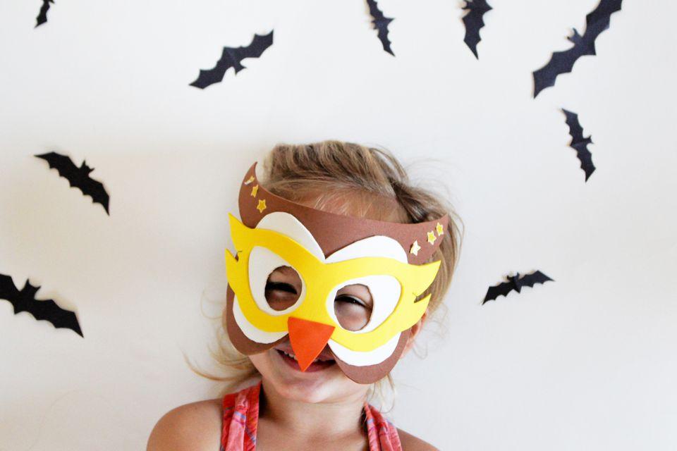 little girl wearing halloween owl mask