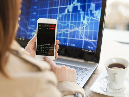 Young woman glance at Stock Market Data on Apple Iphone 8 smart phone