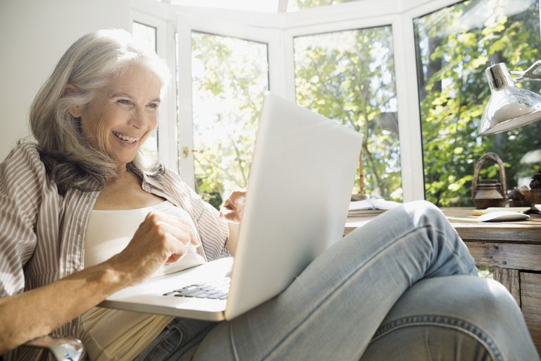 Senior woman using laptop in sunny home office