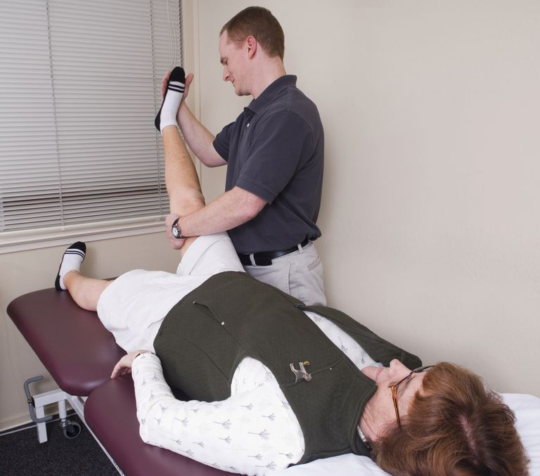 A health practitioner administers the straight leg raise test.