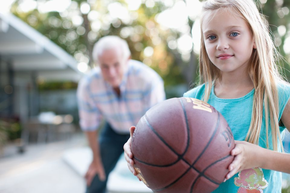 Older man playing basketball with granddaughter