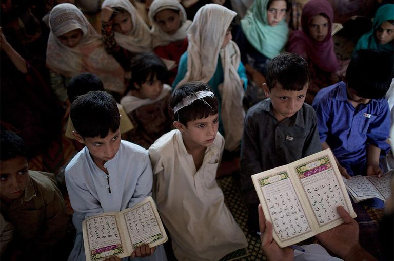 Internally displaced children look on as they recite the Arabic alphabet at a Madrassa