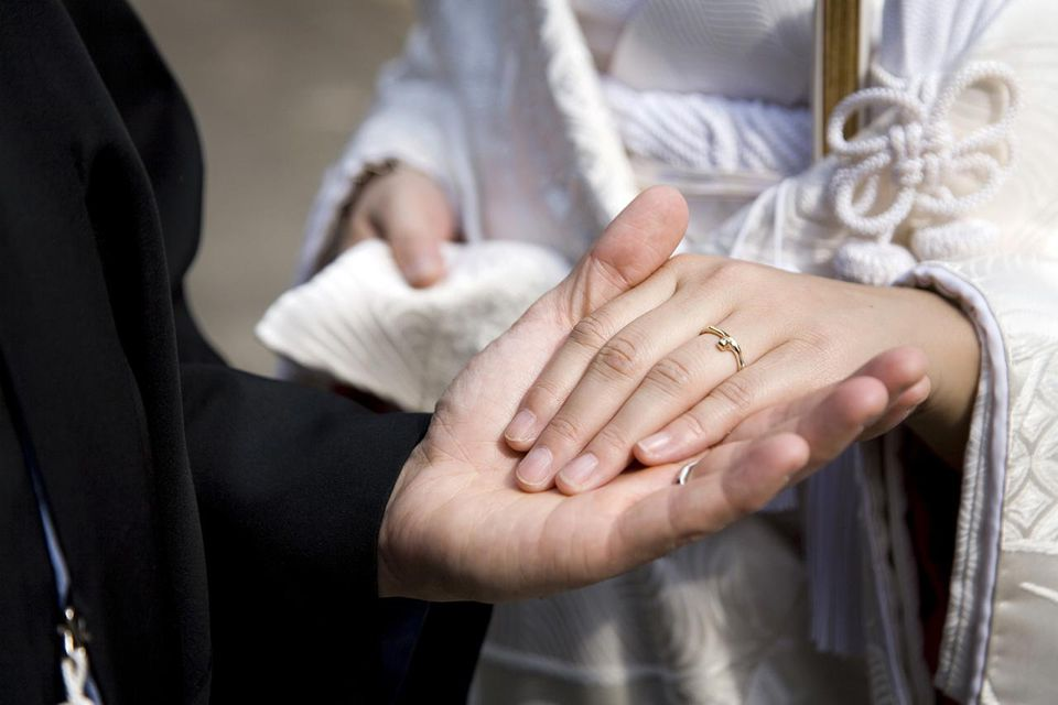 Bride and groom holding hands at wedding ceremony, mid section