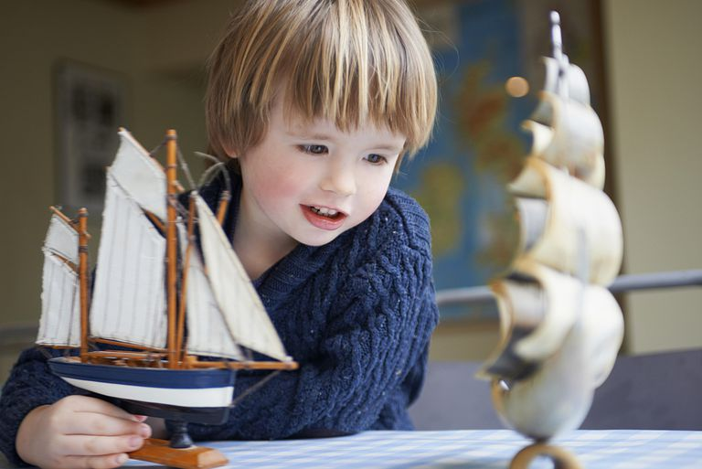 Young boy playing with toy ships