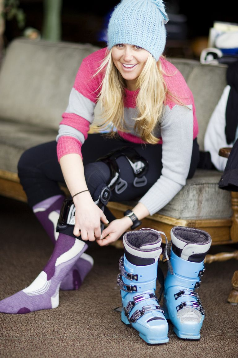 Smiling woman adjusts knee brace with ski boots in foreground