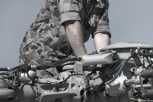 Men repairing helicopter motor & rotor blades