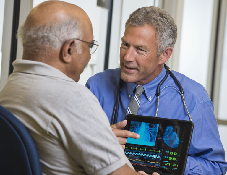 Doctor using digital tablet talking to patient