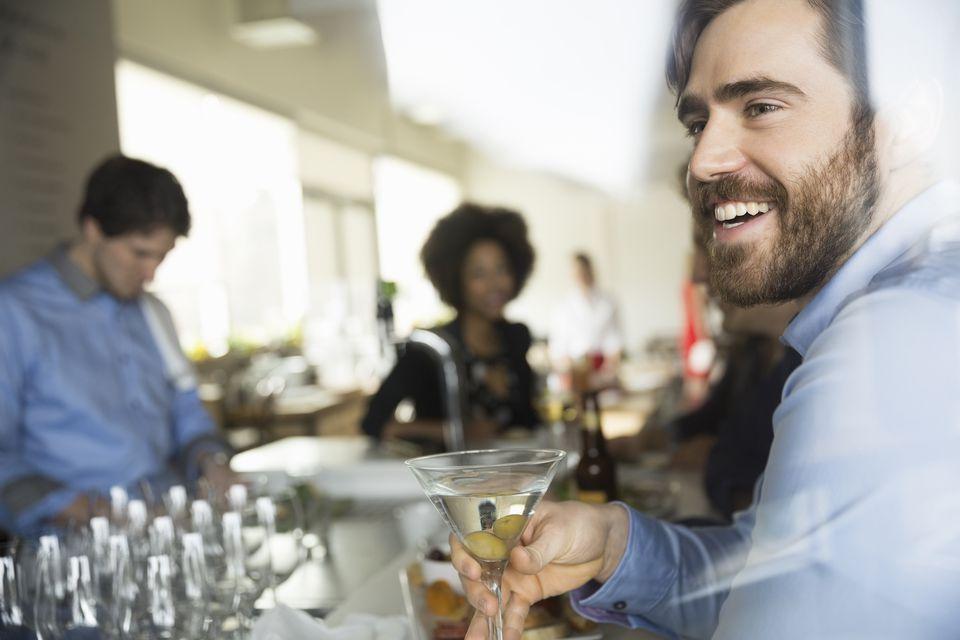 Man enjoying martini at bar