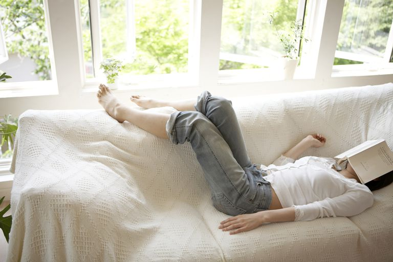 Woman lying on couch with book on face
