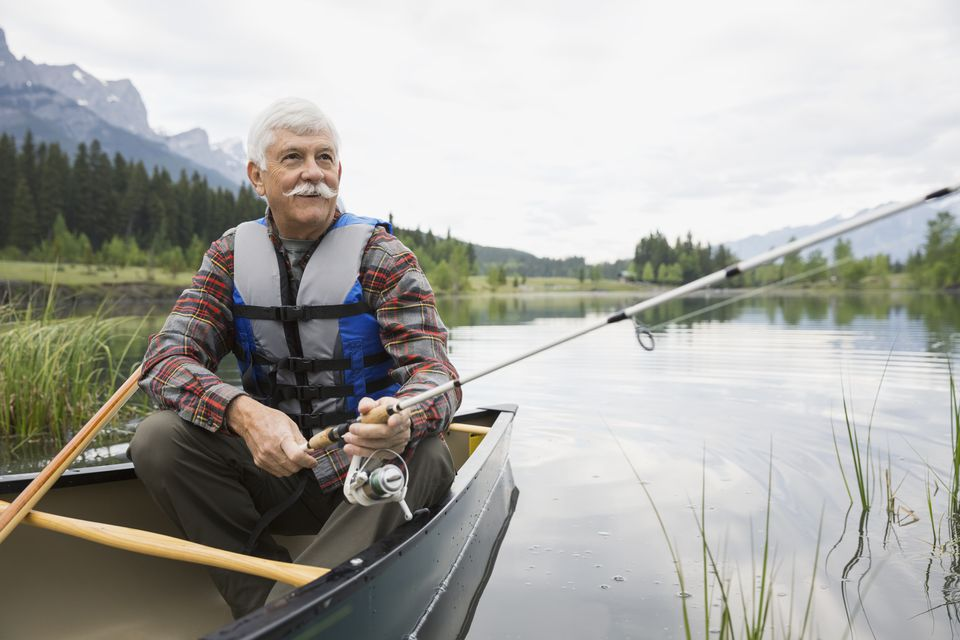Older man fishing in canoe in still lake