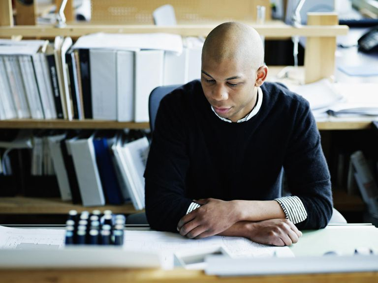 Businessman seated at workstation studying plans