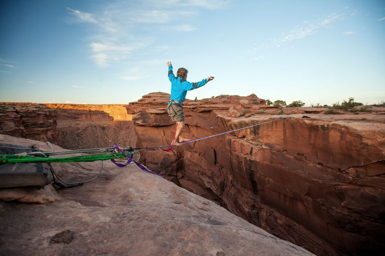 Guy walking on a line over a canyon in Moab