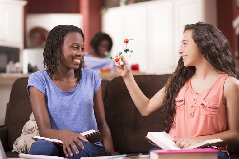 Teenage girls studying DNA molecule, science at home.
