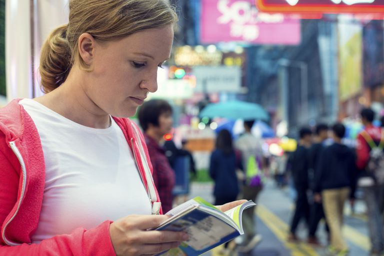 Young tourist checking guide book in Hong Kong street